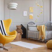 yellow-armchair-teddy-bear-and-crib-in-a-modern-ki-F5JHBNQ-scaled.jpg